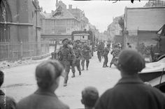 The British 2nd Army: Men of No.46 (Royal Marine) Commando, 4th Special Service Brigade, passing through the village of Douvres la Delivrande, watched by French civilians.