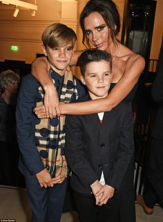 Proud mamma: Victoria Beckham cuddled her sons Romeo and Cruz at the Burberry Festive film premiere after her older son hit the red carpet to promote the fashion house's new seasonal advert, which he stars in