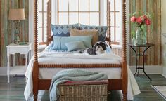 Blue, tan, and cream bedding play off the hues in the weathered wood walls and floor in this rustic country bedroom. Mismatched nightstands and a turned-wood four-poster bed combine for an effortlessly eclectic feel.