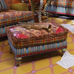 The top of the ottoman is covered in a jewel-tone, woven paisley with red leather caps stitched at each corner, and accented with multicolored brush fringe. Leather Cap, Red Leather, Ottoman Footstool, Ottomans, Kids Furniture, Painted Furniture, Mackenzie Childs Furniture, Mackenzie Tartan, Mckenzie And Childs