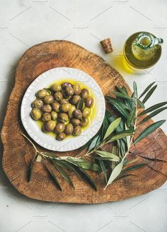 #Pickled green olives  Pickled green Mediterranean olives and olive tree branch on wooden board and virgin olive oil in bottle over grey marble background top view