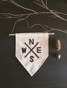 The bigger version of our small compass banner. Handmade. Hand cut, hand sewn felt lettering.    Hanging on a 12 wooden dowel, strung with jute twine