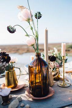 amber bottle centerpieces - photo by Lorenzo Accardi http://ruffledblog.com/winter-beach-wedding-inspiration-in-france