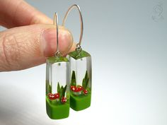 Flying luck – cute fly agaric earrings with red-white spotted plastic mini-mushrooms on a flashy green floor in resin ///// © Isabell Kiefhaber www.geschmeideunterteck.de