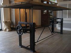 Deze stoere in hoogte verstelbare industriële tafel heeft een gietijzer in hoogte verstelbaar fabrieksonderstel met een mooi doorleefd tafelblad gemaakt van oud eiken wagonplanken. Verstelbaar van 76cm naar 114cm hoog. Te gebruiken als eetkamertafel (laag) of met barstoelen (hoog)