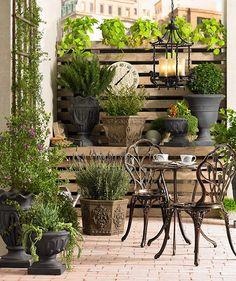 Metal bistro set on brick patio surrounded by plants @lampsplus