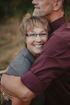 Middle aged woman enjoying a hug from her husband by Rob and Julia Campbell - Stocksy United