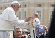 Pope Francis blesses a baby as he arrives to lead the weekly general audience in Saint Peters Square at the Vatican March 27, 2013. Holy Week is celebrated in many Christian traditions during the week before Easter