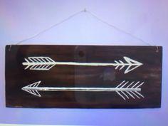 Un cadre avec des flèches. Sélectionnez une planche de bois et avec de la peinture blanche dessinez le modèle de flèche. Vernissez la planche, ajoutez une ficelle et voilà.