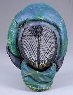 journal - l'antiquaire de l'escrime= Masque de canne et de bâton   vers  1900     épais rembourrage de crin  recouvert de cuir vert  protège nuque double  grillage tressé à larges mailles  ce masque de canne en cuir vert  est vendu     un modèle identique, sans la bavette ,en cuir noir  reste disponible ;  coutures fatiguées , en l'état : 120€