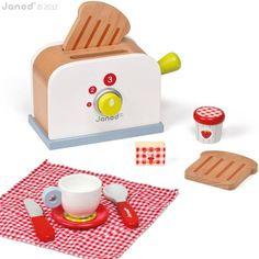 Deze houten broodrooster van Janod past prachtig bij de picknickkoffer en mixer van Janod! Steek de houten sneetjes brood in derooster, stel de temperatuur in, hendel naar omlaag en de sneetjes vliegen eruit! Deze set bevat een broodrooster met 2 sneden brood, een roos-wit geruit stoffen tafellakentje, een houten kopje, schoteltje, mes, lepeltje, boter en confituur. Alles dus voor een lekker en gezellig ontbijt!
