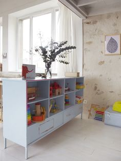 Remove doors from a beat up cabinet, paint, put in living room for neater toy storage