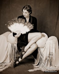 1920s vintage black velvet cape, model seated on a bench with fringed silks, holding a fan with ostrich feathers and peacock feathers