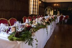 Autumn wedding table decorations. Moss, ferns and ivy together with flowers and berries decorate length of top table. Lympne Castle wedding decorations.