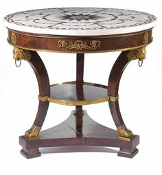 A spectacular early 19th century Russian Empire guéridon with very fine gilt-bronzes. Three sculptural ormolu lionheads support the circular white marble table top inlaid with various precious marbles. (=)