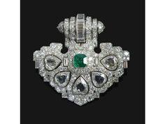 Un important clip en platine et diamants, serti de cinq diamants en coeur de taille ancienne avec en son centre une émeraude taillée à degrés, pouvant se porter en pendentif par lajout dune bélière.Par René DUFOUR, circa 1930.Poids:32 g