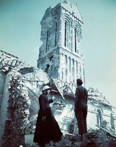 The parish priest, wearing a helmet, converses with Canadian officer atop the ruins of a beautiful church at an unidentified location in France, 1944.