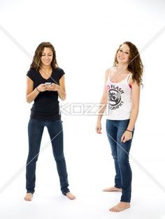 teenage girls with cellphone - Two teenaged girls stand on a white background, one is texting and the other one looks into the camera and smiles