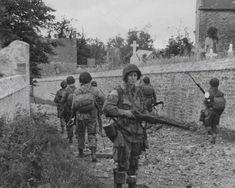 Paratroopers pass through a village churchyard, Normandy.