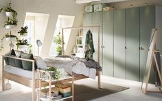 A beige, green and grey bedroom with grey-green wardrobes across the back wall and a wooden bed in the centre.