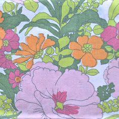 <p>Taie traversin vintage avec un imprimé de fleurs exotiques colorées, légèrement bouloché, état d'usage. Pour apporter une touche douce et vintage à votre chambre ou utiliser le tissu pour une autre création ! On aime ce motif qui évoque encore un peu les vacances !</p>