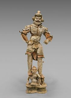 Highly important and rare, very finely modeled Chinese early Tang Dynasty, painted pottery figure; of a well-armored, bearded soldier standing upon a demon; and atop a raised pedestal base; showing much remaining pigments; H: 47""