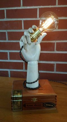 A wooden hand was used to create this unique lamp. Weve used a 12 vintage looking cloth covered cord. The dimmer switch is on the cord. The box is a very nice cigar box that we call a stash box.  Measurements are approximately 7 wide, 15 tall and 6  deep  Ships only to 48 states. Additional charge for outside.  Please like us on Facebook for the latest updates and to find out where we will be selling. https://www.facebook.com/pages/Bartholomews-Brilliant-Boxes/883898391690708