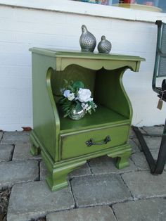 This little end table has been painted in a darker, sort of yellow-y green, distressed and glazed, and the new leafy pull adds to the garden-y feel. Modern Vintage.