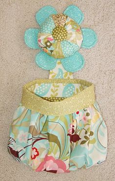 Make a round pincushion like this (instead of a rectangular one) and attach to sewing machine with elastic.