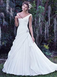 Maggie Sottero - harper, This off-the-shoulder wedding dress exudes femininity with a romantic portrait neckline and layers of Atlie organza. Added elegance is found in the asymmetrical pleated bodice, accented by sparkling Swarovski crystal embellishment at the hip. Finished with corset closure.