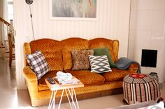 In my living room: Yellow vintage couch, pillows from H&M Home and a fireplace. tuulinenpaiva.fi