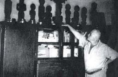 Otto Krohnert mostrando su colección de estatuas fang.