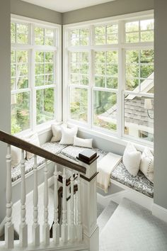 Corner window seat along the traditional stair steps, in classic white with…