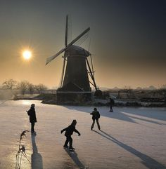 Holland Ice skating near a mill. Typical Dutch winter activity.