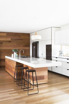 White and wood kitchen. The island base matching the floor seems to make it almost disappear