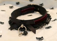 Black lace collar with bells and a red ribbon