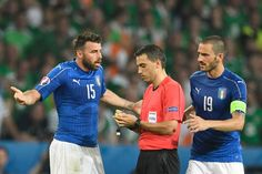 Italy's defender Leonardo Bonucci (R) looks on as Italy's defender Andrea Barzagli (L) gets a yellow card from Romanian referee Ovidiu Hategan (C) during the Euro 2016 group E football match between Italy and Ireland at the Pierre-Mauroy stadium in Villeneuve-d'Ascq, near Lille, on June 22, 2016. / AFP / MIGUEL MEDINA