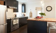 Black kitchen with butcher block island and stainless steel appliances #IncomeProperty