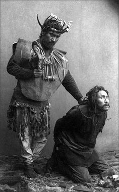 Tlingit Indian shaman holding rattle and standing over kneeling man. ca. 1886. This photo appears to be posed for and taken in a studio setting. Both men have made the scene quite frightening.