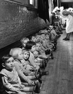 A nurse looks over a row of toddlers who sit along a wall as World War II evacuees, at a nursery in Middlesex, England. 1941.