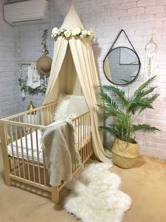 The Avery canopy creates the most welcoming, peaceful and serene decor in your baby's nursery. Enclosing your little baby in their cot, crib or bed away from the busy world for a sweet slumber or in an older kids bedroom as a quiet reading nook as a statement piece of decor. I love that the canopy can grow with your child adapting to an array of uses. #nurseryideas #babyroom #furrug #homeplant #mirrior #whitebrickwall #canopy #flowercrown #woodencrib