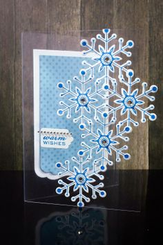 handmade Christmas card: stamped and punched out snowflakes on a clear acetate card ... solid tag in matching blue for message inside ...