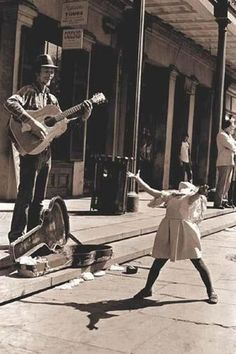 Candid photo of a jubilant youngster entertained by a street musician.  Sing out, girl!