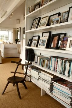 A great idea for a hallway - shelves to hold books and framed photos and art.