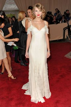 Taylor Swift Evening Dress - Taylor Swift toned down the beads and sparkle for the MET Gala and showed off this stunning off-the-shoulder white dress.  Brand:  Ralph Lauren