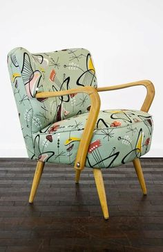 Barkcloth upholstery and the futuristic design of the chair make a wonderful addition to any Atomic Age Mid-Century Modern room.