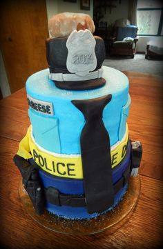 3 tier Police cake for a young man graduating from the Police Academy! 10 inch 2 layer rounds, 9 inch single layer, 8in 2 layer! All buttercream and candy clay details, no fondant here! Police hat made from rice krispy treats and candy clay, with a Der Dutchman doughnut topping it off! All edible! https://www.facebook.com/angelas.cakes2011