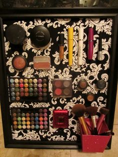 Use a sheet of metal, cover it with fabric, glue the fabric in place and glue magnets to the back of your makeup products to make them stay on the metal.