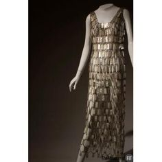 Designer: Paco Rabanne 1934- Medium: Plastic and metal Date: c.1968 Country: France Credit: Gift of Montgomery Ward This example of Paco Rabannes chain mail designs was intended as a wedding dress for an ultra-modern bride. Surprisingly sleek, this maxi-length gown with a deep, V-back is constructed of white, silver, and pearlescent plastic rectangles linked by metal loops.