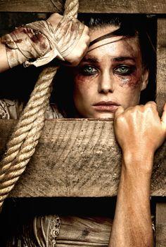 1) Je ziet een afbeelding van een vrouw achter een soort houten schutting met wonden aan haar hand en gezicht. 2) je kan zien dat de vrouw aan het vechten is om vrij te komen op de stevige manier hoe ze de plank vast houdt.